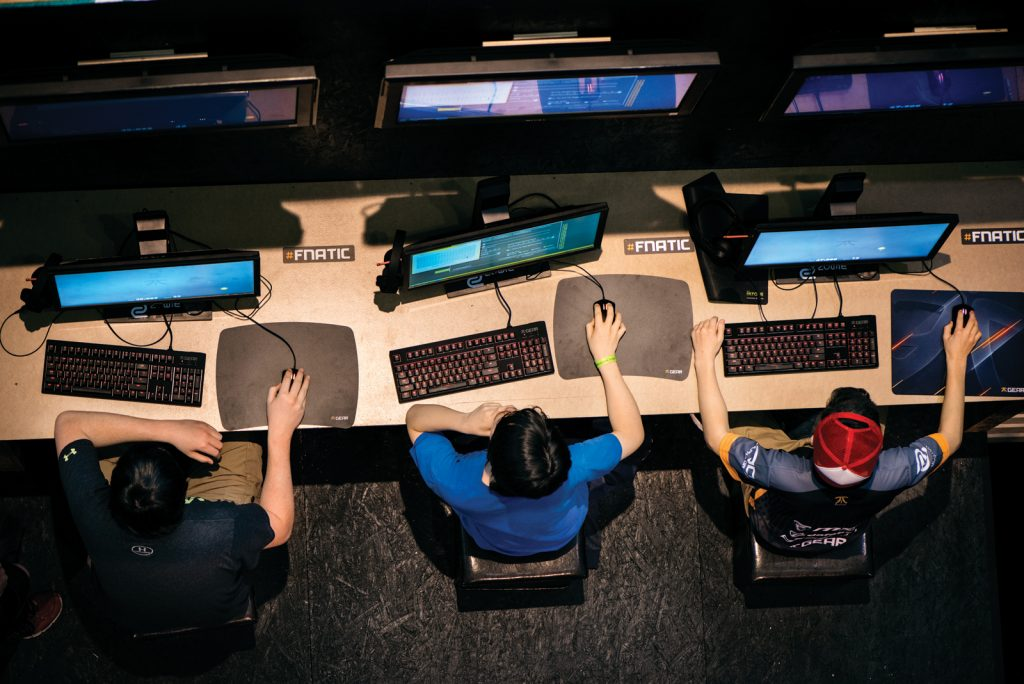 Young men play a game which tests mouse precision and timing during the MLG Finals in Columbus, Ohio.